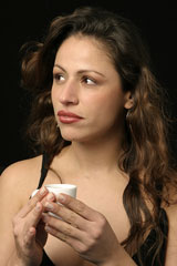 pensive Brazilian woman, holding a cup of coffee